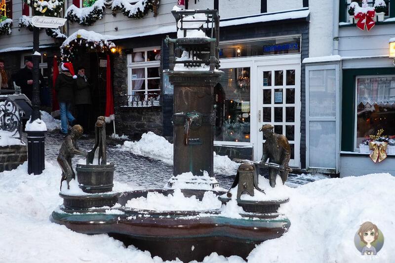 Ein wunderschoener Brunnen in der Altstadt von Monschau in der Eifel