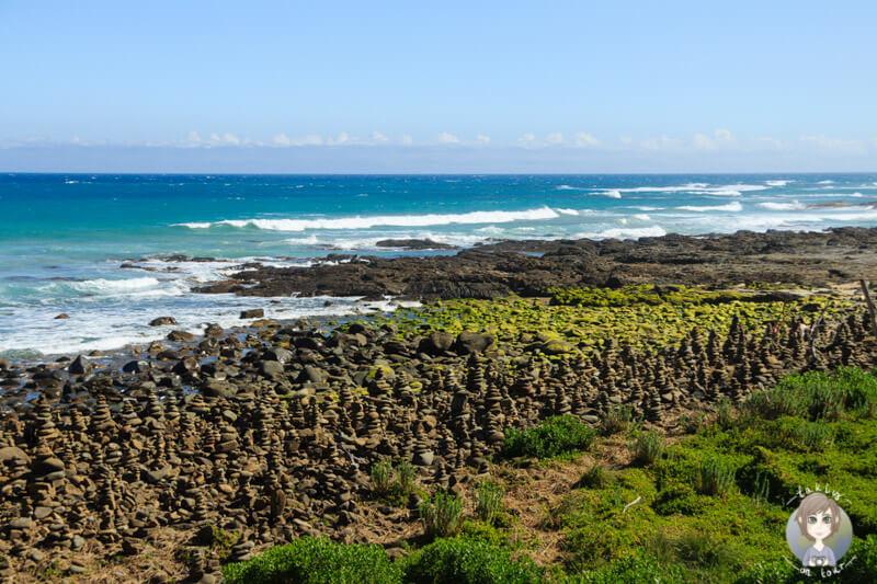 Ein Strand mit kleinen Steinhäufchen