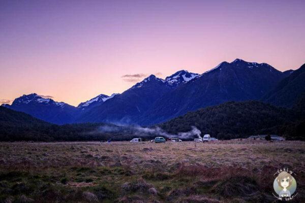Sonnenuntergang auf dem Cascade Creek Campground mit Blick auf die Berge ist einer der beliebtesten Campingplaetze in Neuseeland entlag der Milford Road