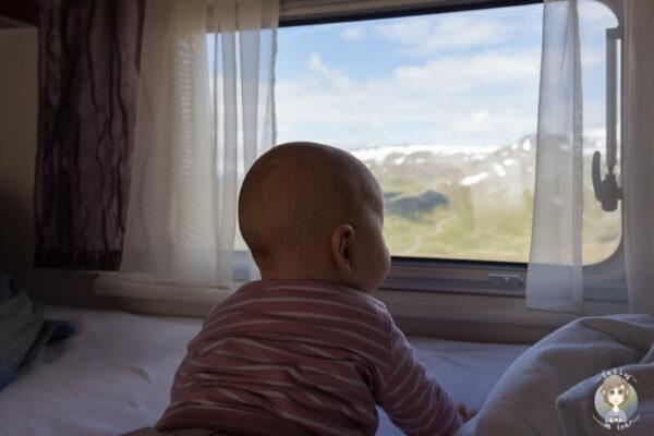 Ein Baby schaut aus einem Fenster auf einer Reise mit Baby im Wohnmobil