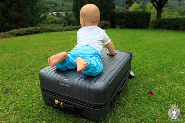 Ein Baby auf einem Koffer bereit zum Reisen in der Elternzeit