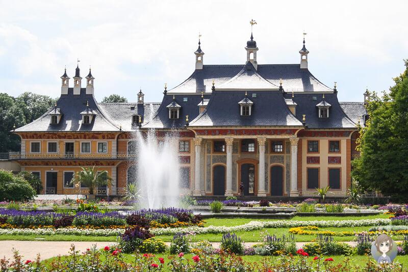 Das bunte Schloss Pillnitz mit Springbrunnen und bluehendem Garten davor