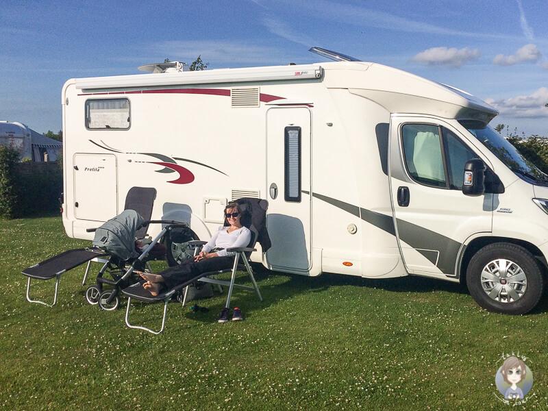 Mutter sitzt auf Campingstuhl neben Kinderwagen vor dem Wohnmobil Dinge die man auf einer Wohnmobilreise mit Baby braucht