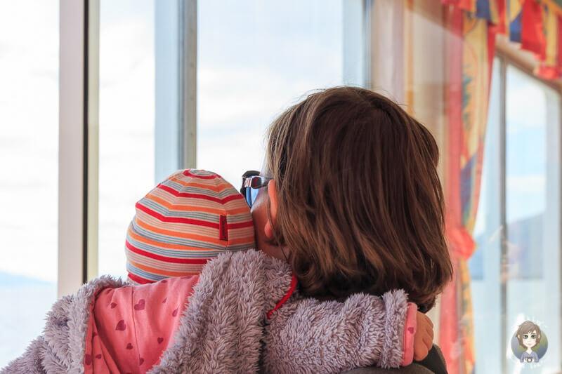 Blick aus dem Fenster von Mutter mit Baby