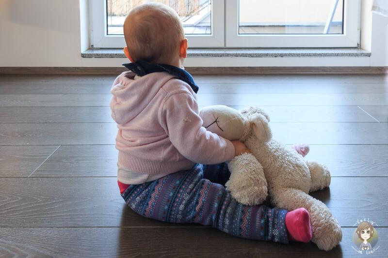 Baby mit Kuscheltier sitzt auf dem Boden