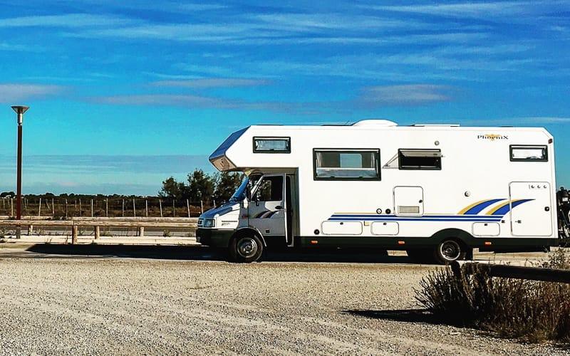 Ein Wohnmobil auf einem Schotterplatz bei blauem Himmel
