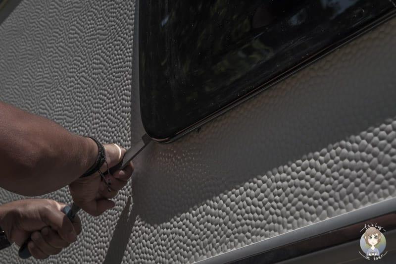Ein Einbrechner versucht ein Wohnmobilfenster aufzuhebeln dazu dient Wohnmobil Sicherheit