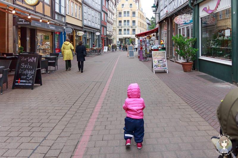 Ein Kleinkind läuft entlang dem Roten Faden auf einem Citytrip nach Hannover mit Kind