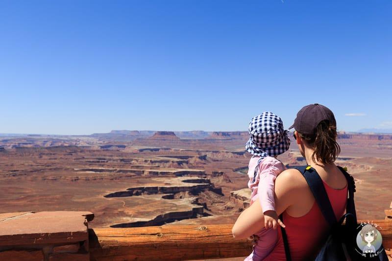 Ein Kind schaut auf dem Arm seiner Mama während einer Fernreise mit Kindern auf einen Canyon in den USA