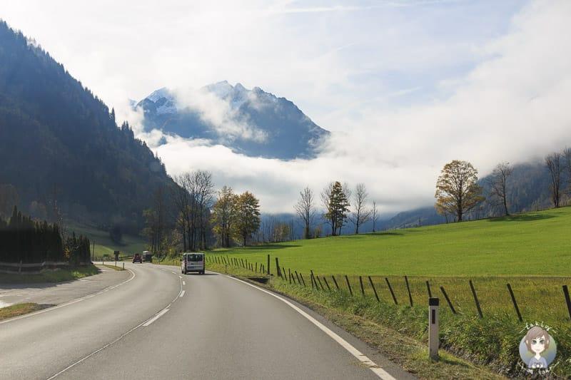 Fahrt durch ein Tal in Österreich mit tiefhängenden Wolken