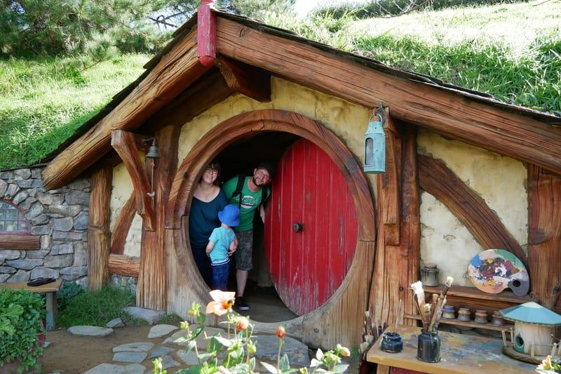 Familie in Hobbiton auf einer Reise durch Neuseeland mit Kind
