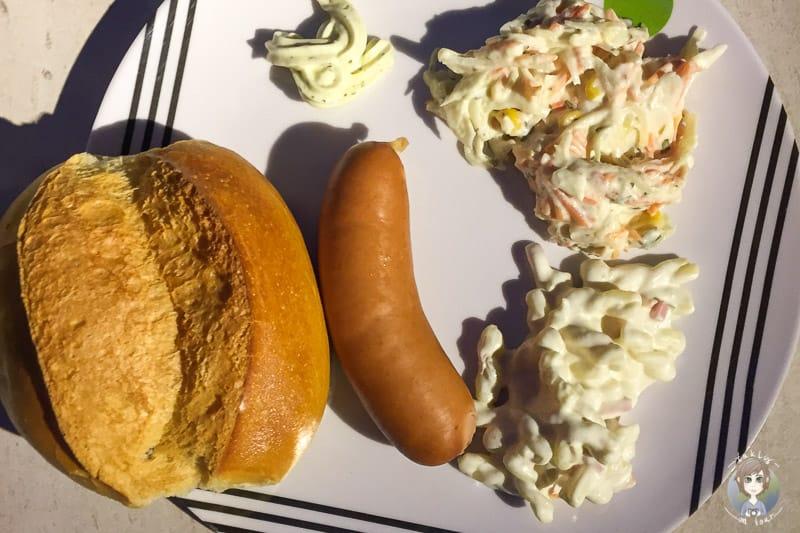 Ein Brötchen mit Würstchen und Salat ist ein leckeres Campingrezept