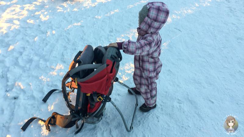 Kleine Pause mit Kind und Kraxe im Schnee