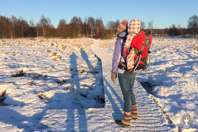 Wandern mit Kleinkind in der Kraxe im Schnee