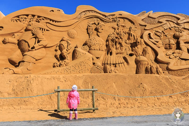 Ein Kind vor einem Meisterwerk auf dem Das Sandskulpturenfestival in Sondervig