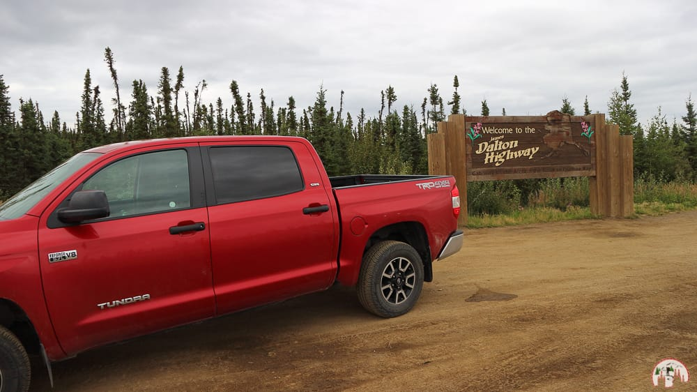 Roter Pickup Truck am Dalton Highway Schild
